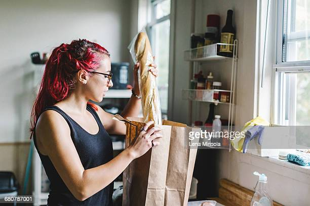 Young woman with pink hair unpacking baguette from shopping bag in kitchen