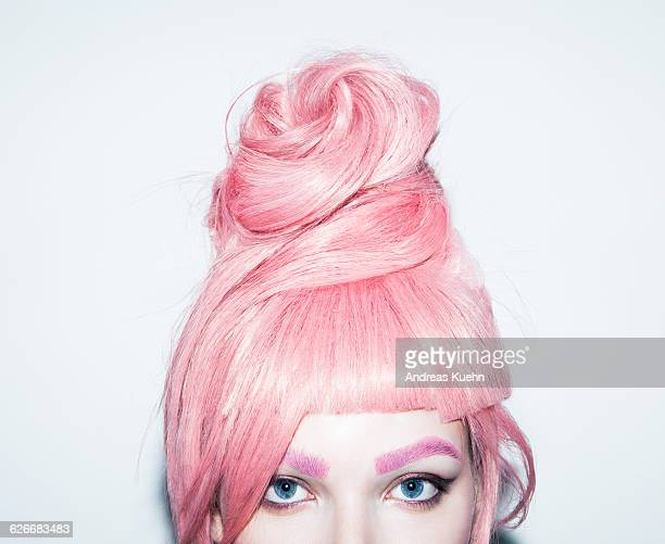 Young woman with pink hair wig in an updo, crop.