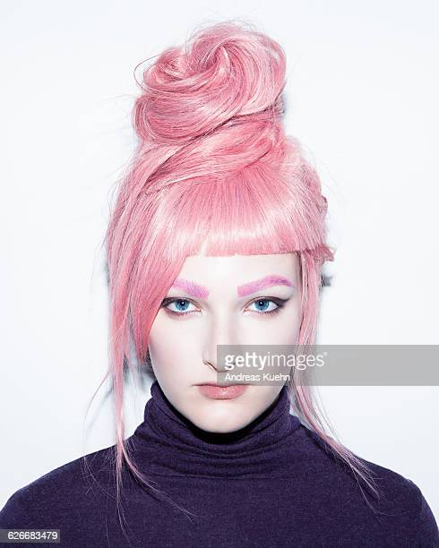 Young woman with pink hair wig in an updo.