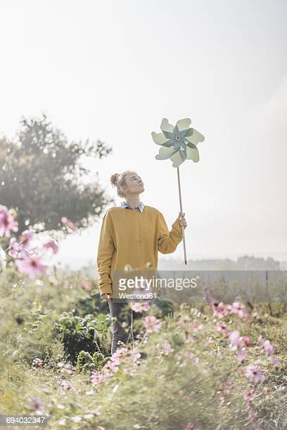 Young woman with pinwheel in cottage garden