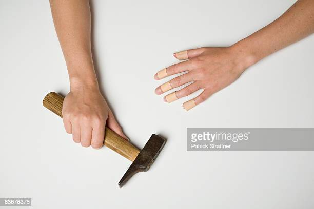 A young woman with plasters on all fingers of one hand and in the other hand is a hammer