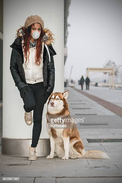 Young woman with pollution mask and her dog