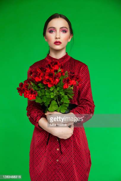 young woman with potted flower - 赤のドレス ストックフォトと画像