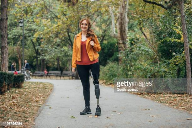 young woman with prosthetic leg standing at park - amputee woman stock pictures, royalty-free photos & images
