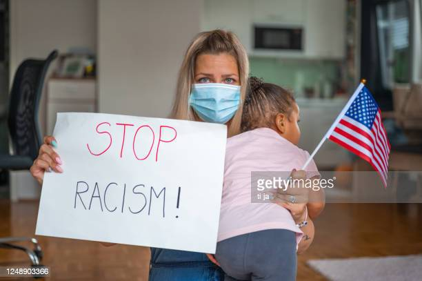 young woman with protective face mask holding a child and a poster with a message: stop racism! - fight for families rally stock pictures, royalty-free photos & images