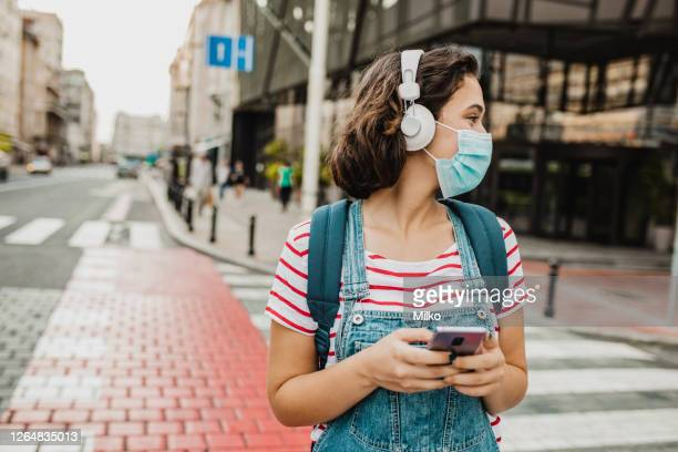 young woman with protective face mask is using mobile phone - listening stock pictures, royalty-free photos & images