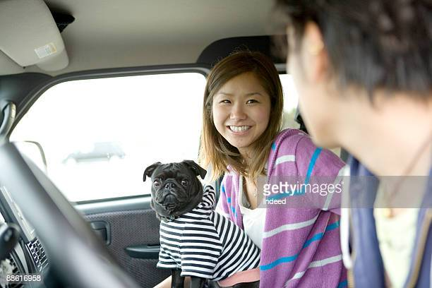 Young woman with pug looking at man in car