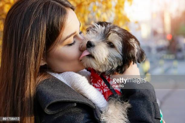 young woman with puppy outdoors - coat stock pictures, royalty-free photos & images