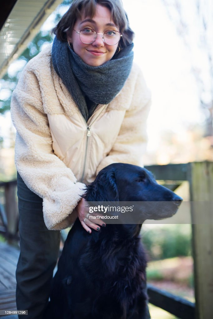 Young woman with purebred flat-coated retriever. : Stock Photo