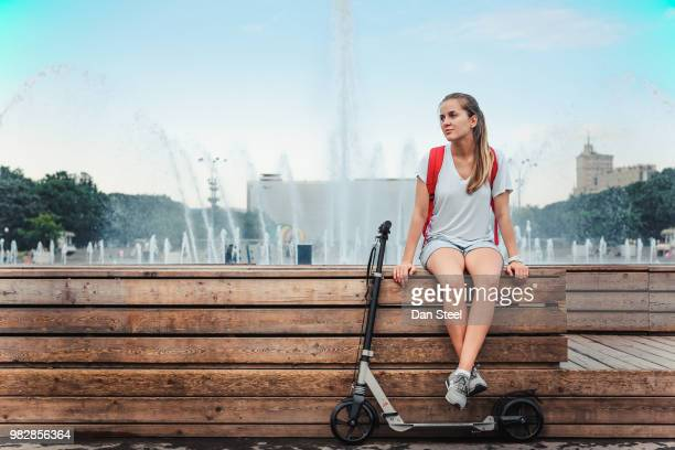 young woman with push scooter sitting in park, moscow, russia - femme fontaine photos et images de collection