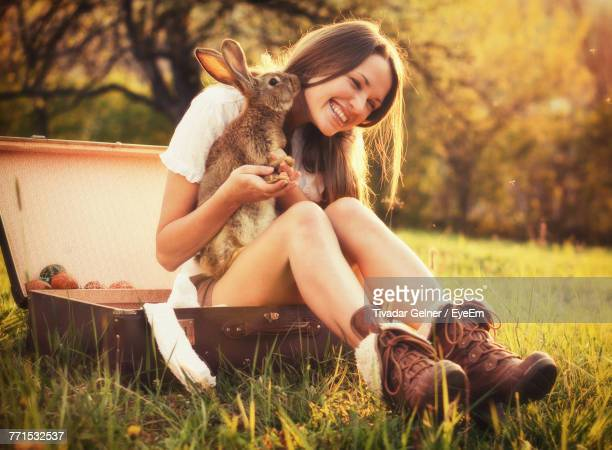 young woman with rabbit sitting on field - lagomorphs stock pictures, royalty-free photos & images