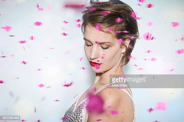 Young woman with rain of pink confetti