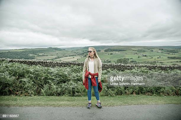Young woman with raincoat on moorlands