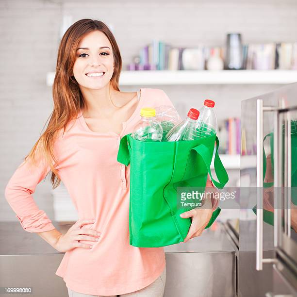 Young woman with recycling bag full of bottles