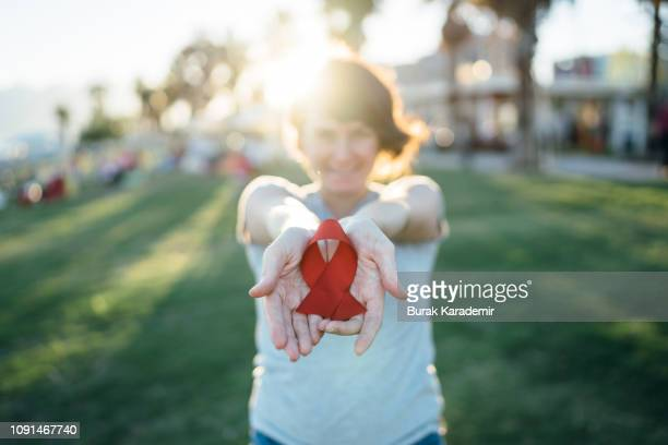 young woman with red aids awareness ribbon - hiv stock pictures, royalty-free photos & images