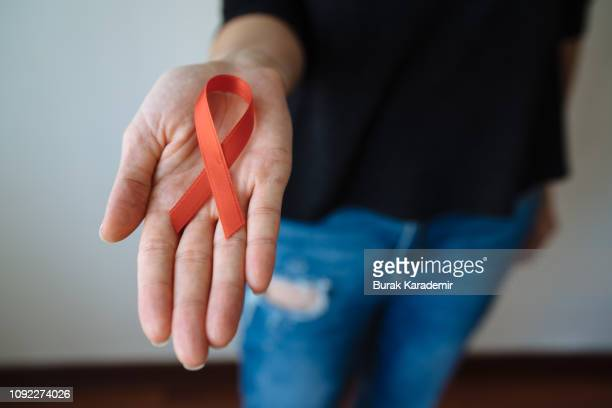 young woman with red aids awareness ribbon - aids stock pictures, royalty-free photos & images