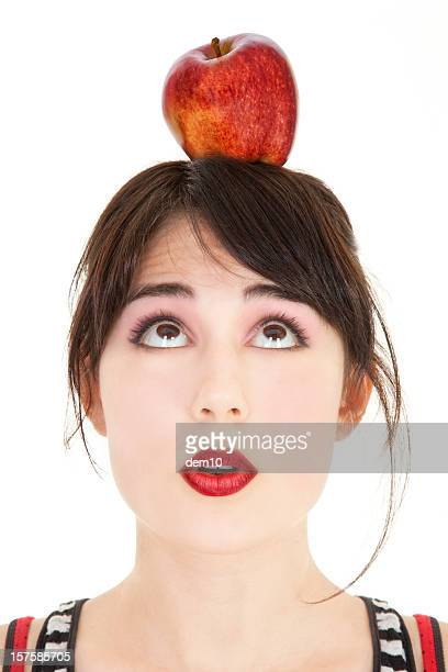 Young woman with red apple on top of head
