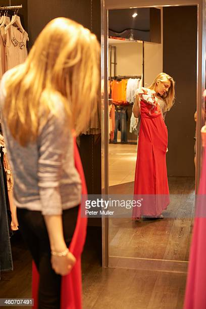 Young woman with red dress in fitting room