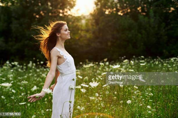young woman with red hair in a beautiful white dress in nature, harmony and freedom - 白のドレス ストックフォトと画像