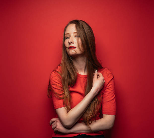 Young woman with red hair on red background