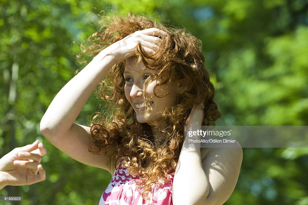 Young woman with red hair outdoors on windy day : Stock Photo