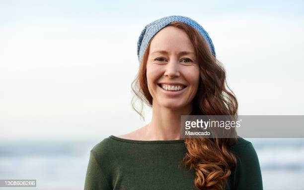 young woman with red hair smiling while standing by the ocean - one young woman only stock pictures, royalty-free photos & images