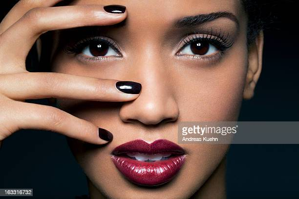Young woman with red lips and black nail polish.