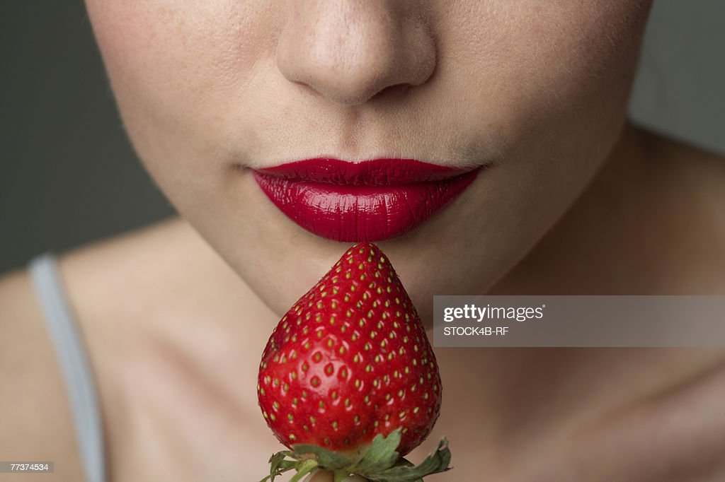 Young woman with red lips eating a strawberry (part of), close-up : ストックフォト