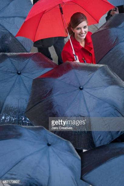 Young woman with red umbrella amongst black umbrella's