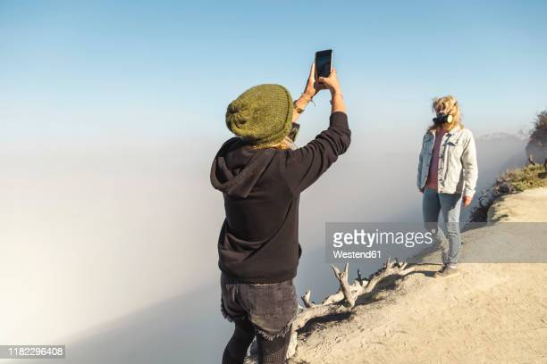 young woman with respirator mask taking a photo of her girlfriend at the edge of volcano ijen, java, indonesia - java stock pictures, royalty-free photos & images