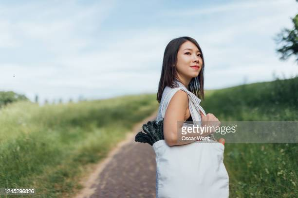 young woman with reusable shopping bag walking at the park - copy space stock pictures, royalty-free photos & images