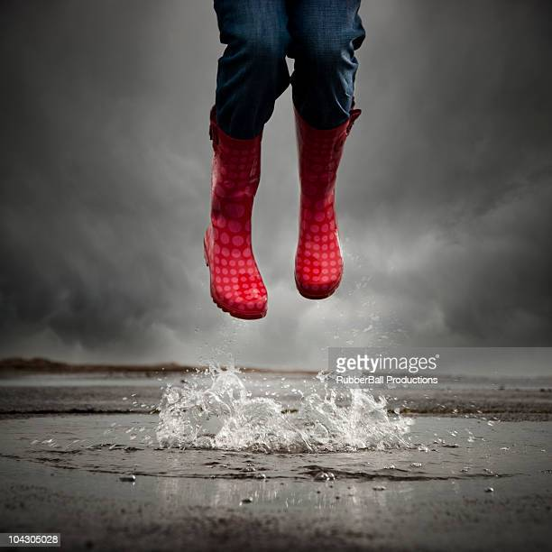 young woman with rubber boots jumping in puddle,low section - puddle stock pictures, royalty-free photos & images
