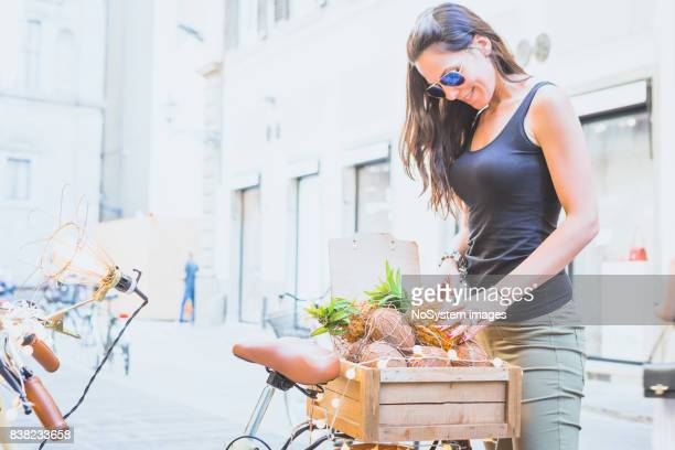 Young woman with rural bicycle, fruit in wicker basket.