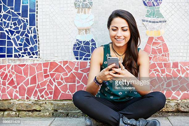 Young woman with sat with smartphone, mosaic wall.