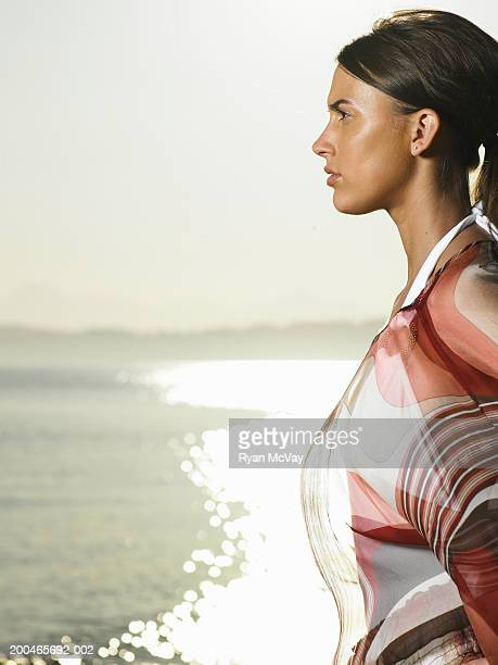 Young woman with sea in background, side view