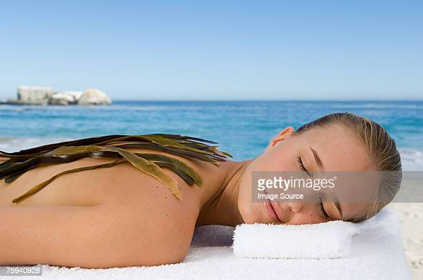 Young woman with seaweed on her back