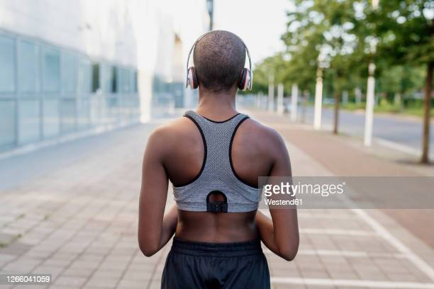 young woman with shaved head listening music through headphones while standing on footpath - shaved stock pictures, royalty-free photos & images