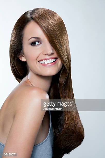 Young woman with shiny hair smiling, portrait.