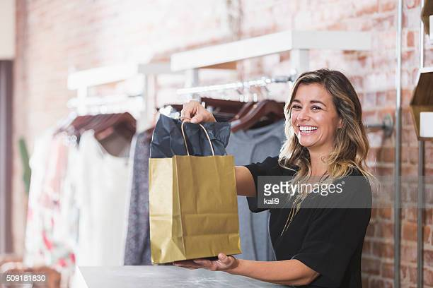 young woman with shopping bag in clothing store - winkelen stockfoto's en -beelden