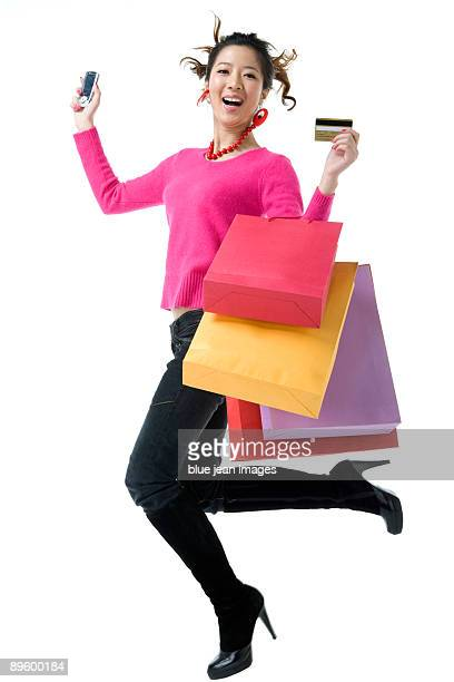 Young woman with shopping bags, credit card and mobile phone leaping