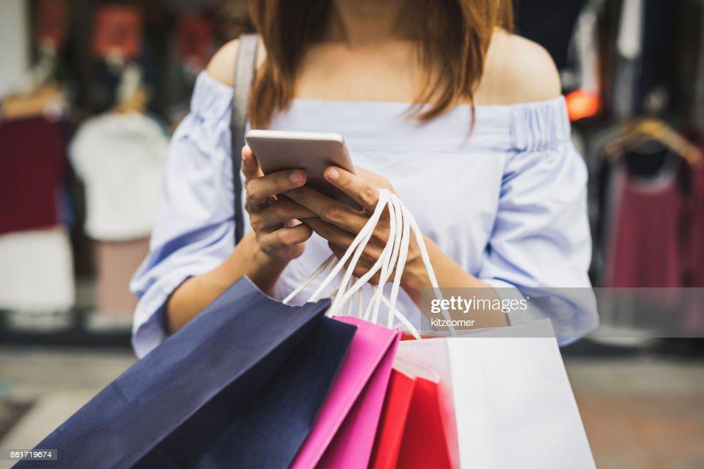 Jonge vrouw met boodschappentassen in de winkel : Stockfoto