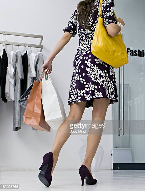young woman with shopping bags leaving store - shoulder bag stock pictures, royalty-free photos & images