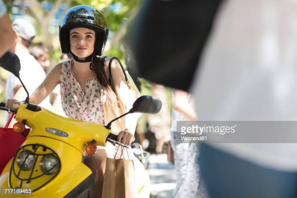 Young woman with shopping bags on motor scooter