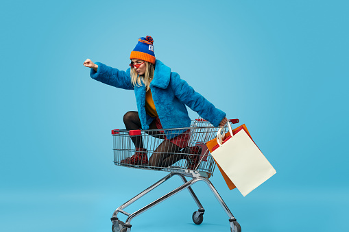 Young woman with shopping bags riding trolley 1157459058