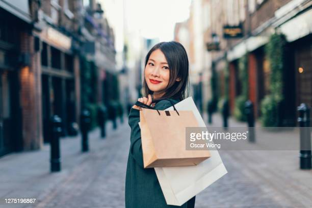 young woman with shopping bags walking on city street - buying stock pictures, royalty-free photos & images