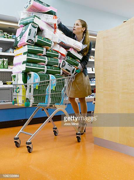 young woman with shopping cart - excesso imagens e fotografias de stock