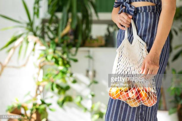 young woman with shopping cotton eco bag with fruits and vegetables in her hands on green wall background. lifestyle, zero waste concept - tote bag stock pictures, royalty-free photos & images