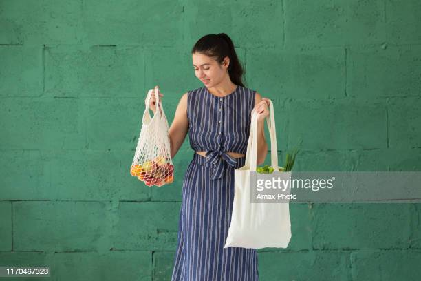 young woman with shopping cotton eco bag with fruits and vegetables in her hands on green wall background. lifestyle, zero waste concept - mesh textile stock pictures, royalty-free photos & images