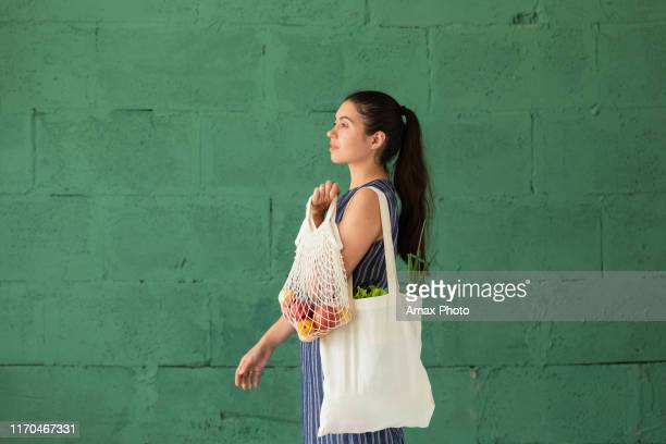 young woman with shopping cotton eco bag with fruits and vegetables in her hands on green wall background. lifestyle, zero waste concept - consumerism stock pictures, royalty-free photos & images