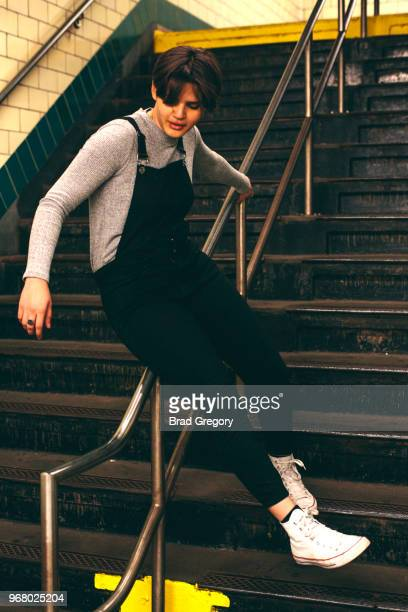 young woman with short hair sliding down handrail in nyc subway station - androgyn stock-fotos und bilder
